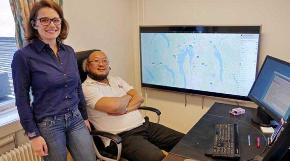 Sonja og Kenneth hos AEX er fornøyde foran webportalen som henger i storskjerm på veggen